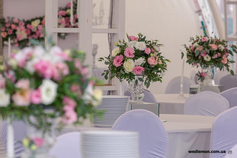 Скляна ваза на ніжці з квітами на стіл для гостей