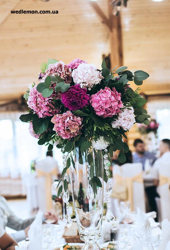 декор гостьових столів на високих формених скляних вазах з обємними квітковими композиціями