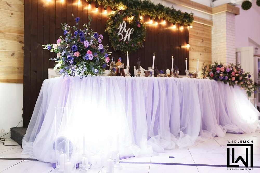 Оформлення весілля Львів, стіл молодят в бузковій спідничці, заднік за молодими з дошок, зелень та ретро гірлянди. Пишний віночок з квітів та зелені та звісно ініціали молодят