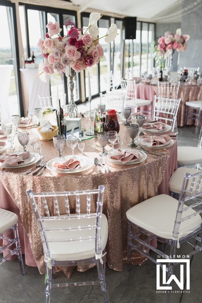 оформлення столів гостей на весілля, високі срібні вази з пишними композиціями, скатертини на столах