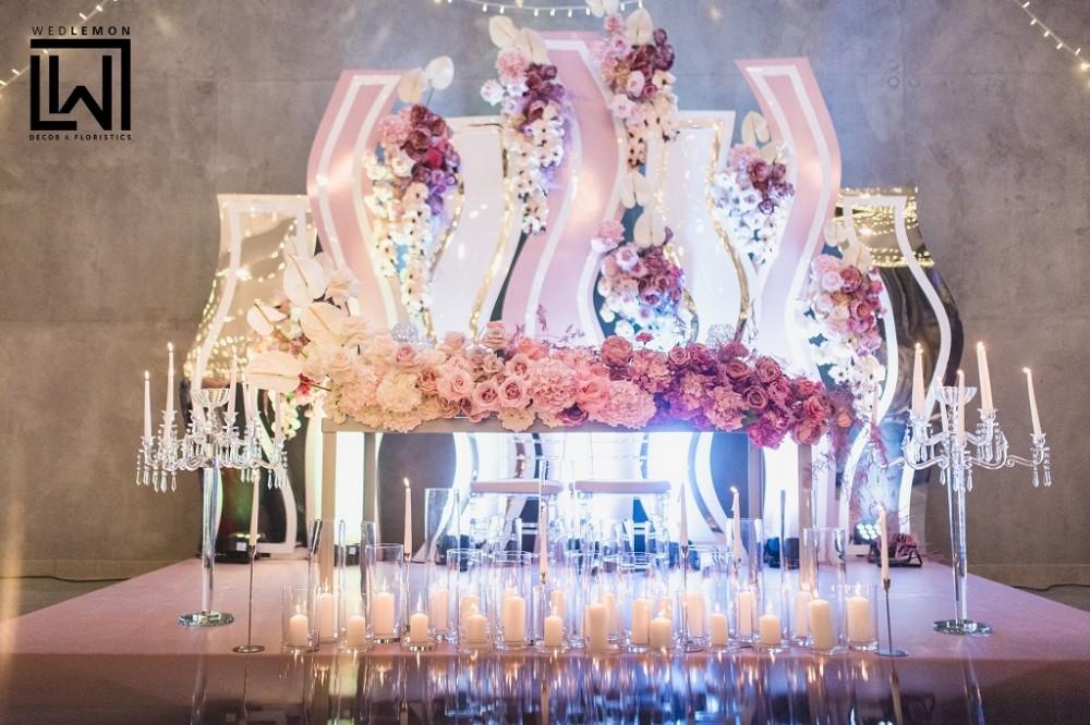 Прозорі підсвічники, вази зі свічками, формлення столу молодих квітами та шикарнем декораціями за молодими. Президіум молодих сіяв та світився