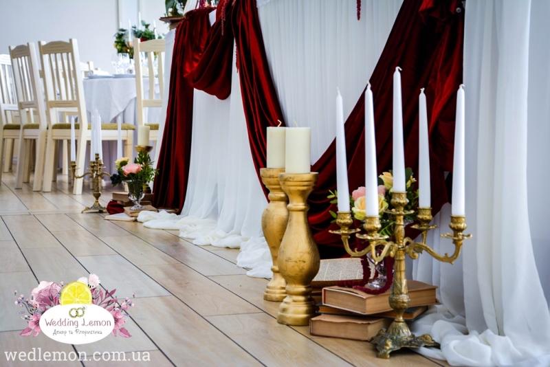 декор перед столом молодих золотий підсвічник та свічки
