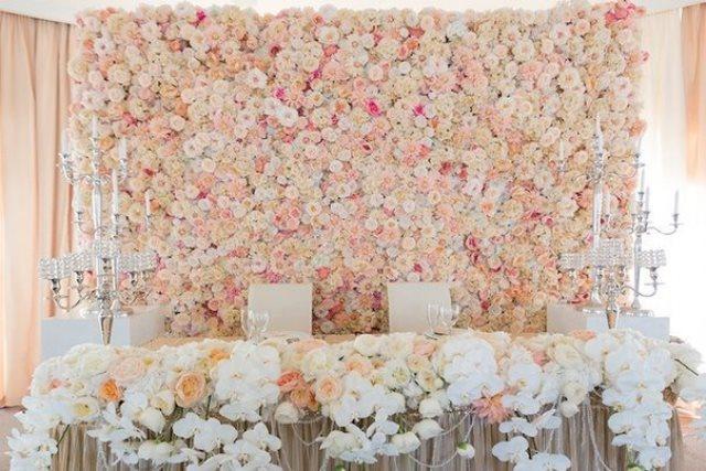 Стінка за молодятами оформлена квітами